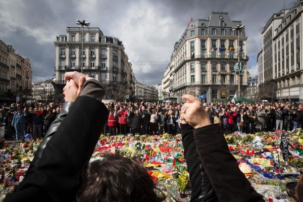 People hold hands as they gather at the makeshift memorial on the Place de la Bourse Square, on March 27, 2016, in Brussels to pay tribute to the victims of the Brussels terror attacks which killed 31 people and injured over 300. Photo - AFP
