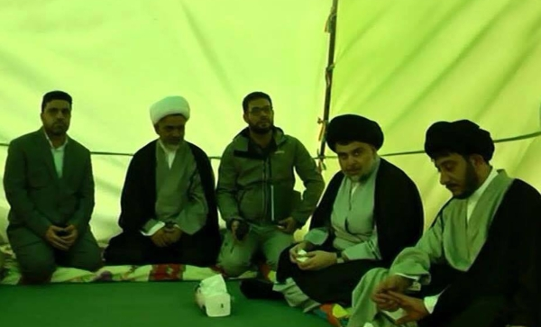 A handout picture provided by the press office of Iraqi cleric Moqtada Al Sadr shows him, second from right, sitting in a marquee as he begins a sit-in protest inside Baghdad's fortified