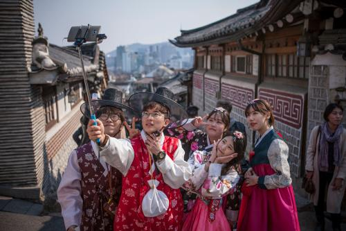 Young Koreans take a selfie as they walk around the Samcheongdong area of Seoul wearing traditional Korean dress