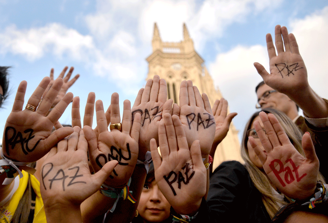 "Colombians raise their hands with the word ""peace"" during an event in Bogota in June 2014. AFP/Diana Sanchez"