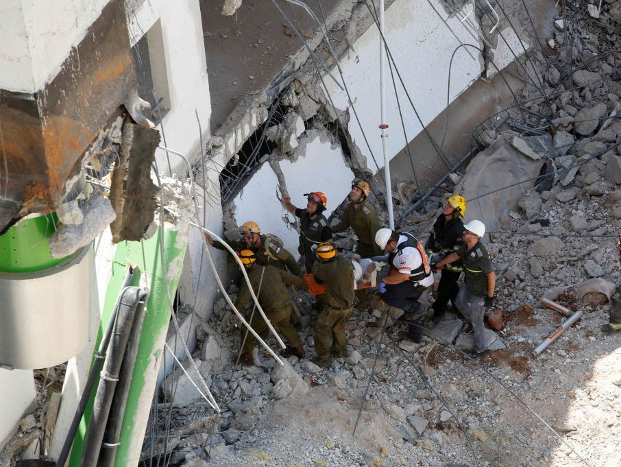 Israeli medics and emergency units carry a wounded person away on a stretcher from a construction site after an underground car park collapsed on Sept. 5 in Tel Aviv.