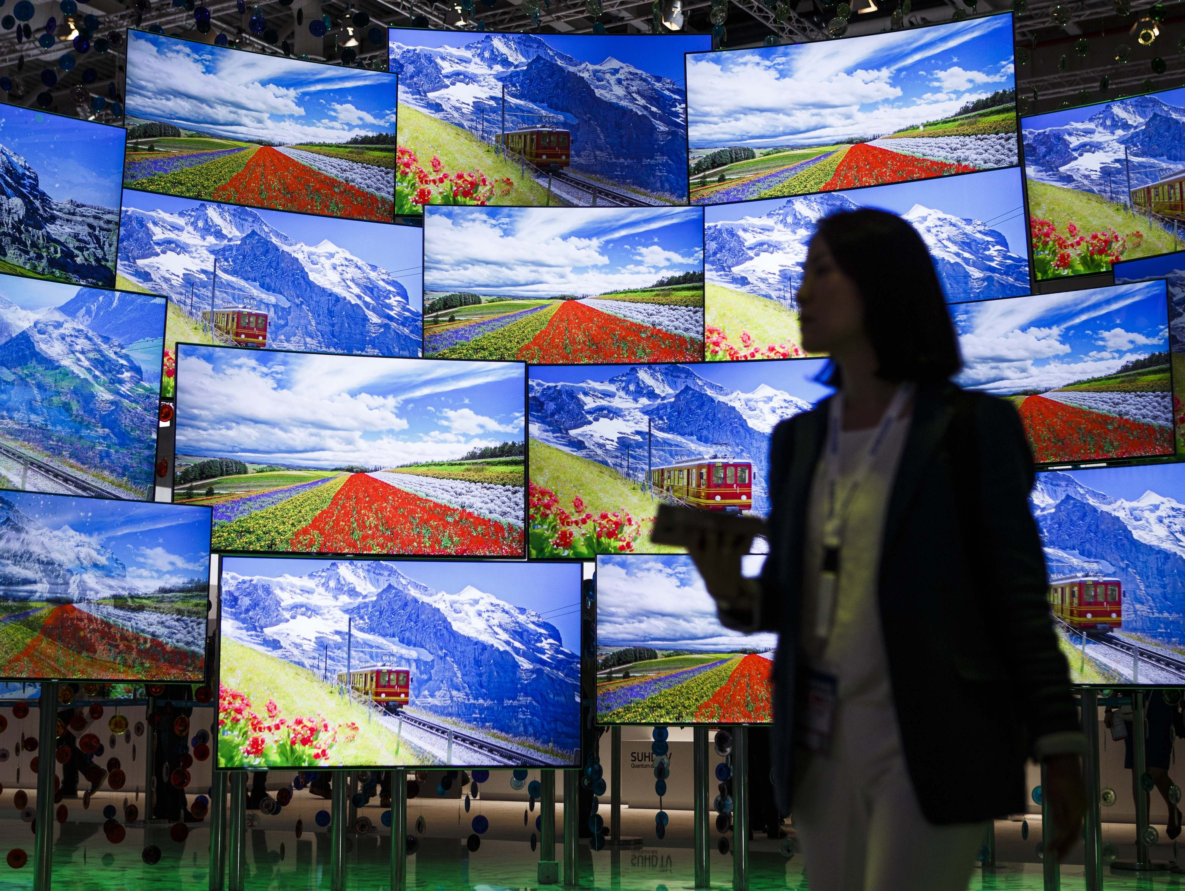 A visitor passes the display wall from Samsung at the 2016 IFA consumer electronics trade fair in Berlin, Germany.