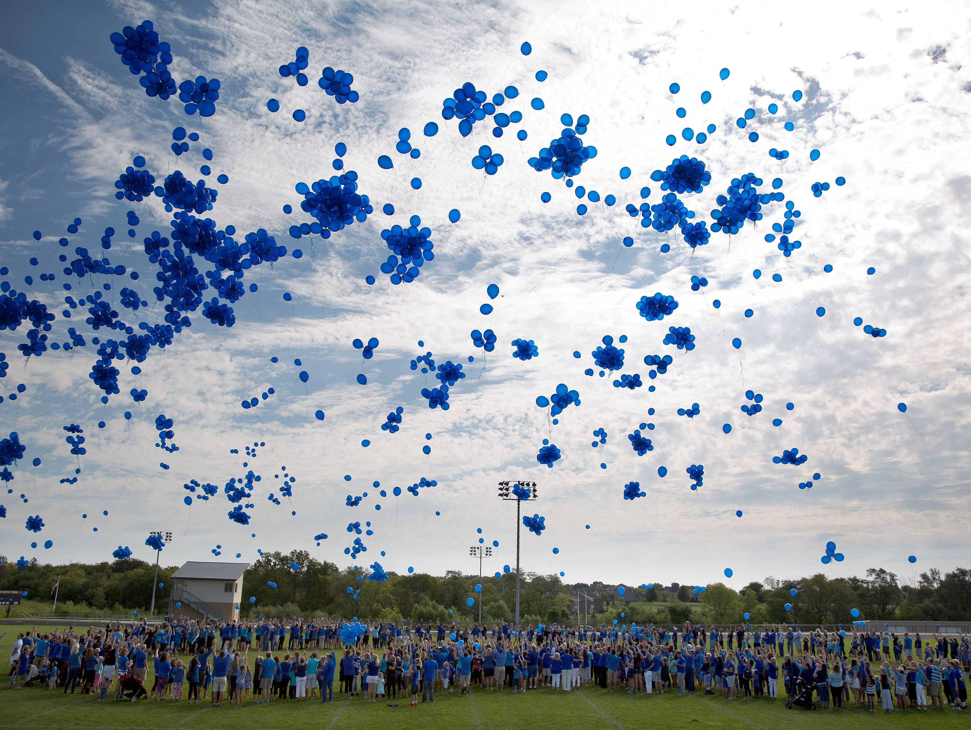 In this Saturday, Sept. 3, 2016, photo, community members release blue balloons while standing in the formation of a heart during a Love for Lane Celebration on what would have been Lane Graves' third birthday, in Omaha, Neb. The parents of the toddl