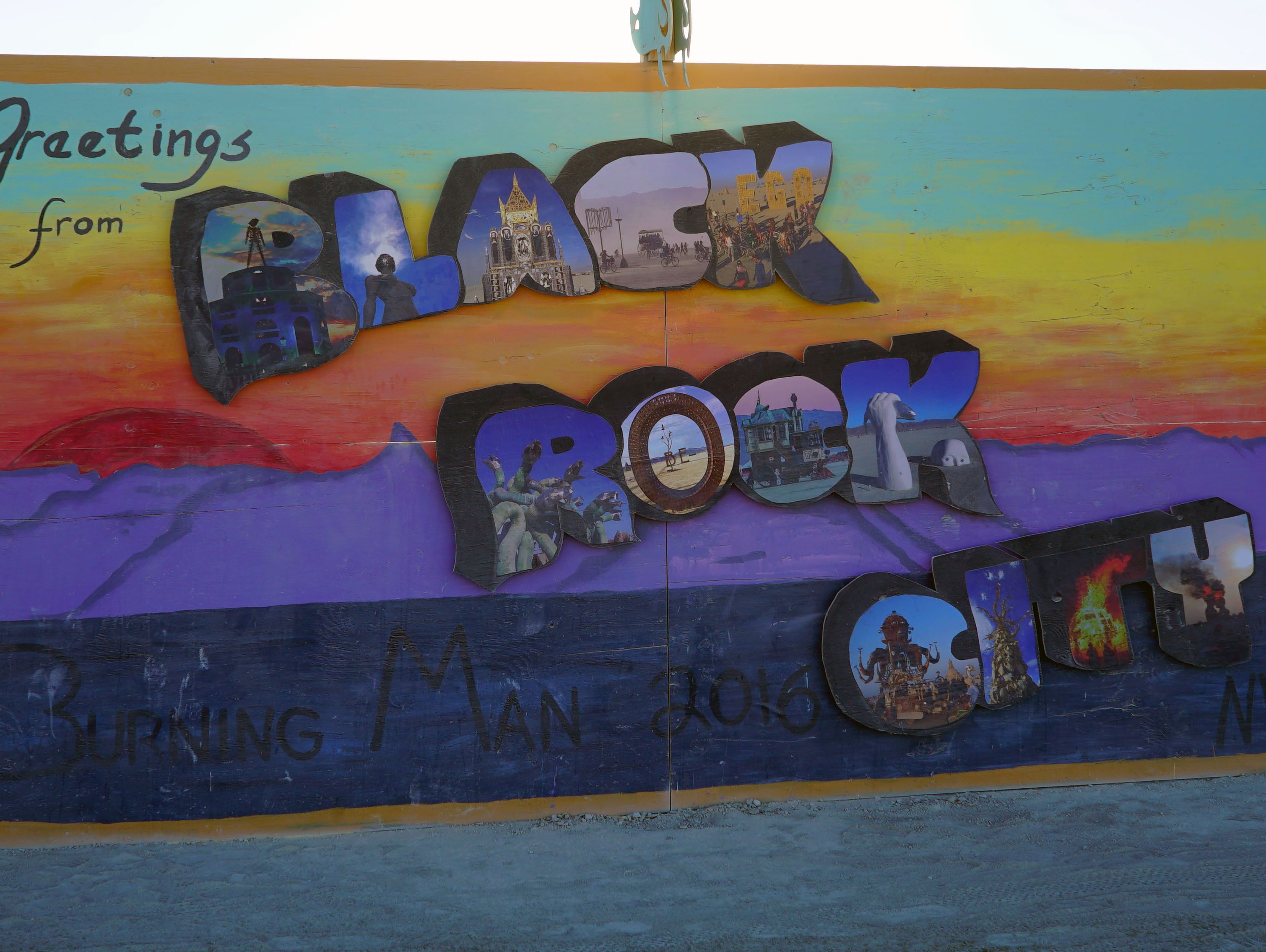 A hand-lettered billboard inside Burning Man's encampment welcomes visitors to the 70,000-person temporary civilization built in the Black Rock Desert for a week on Sept. 1, 2016.