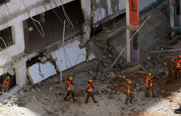 Israeli rescue workers walk at the site where a building collapse on September 5, 2016 in the Ramat Hahayal neighbourhood in the coastal city of Tel Aviv. Photo - AFP